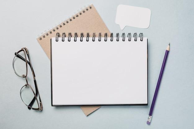 Notizblock, weißer aufkleber, pensil und brille auf dem schreibtisch. verspotten sie im hintergrund des kopierraumbüros. es ist wichtig, die notiz nicht zu vergessen