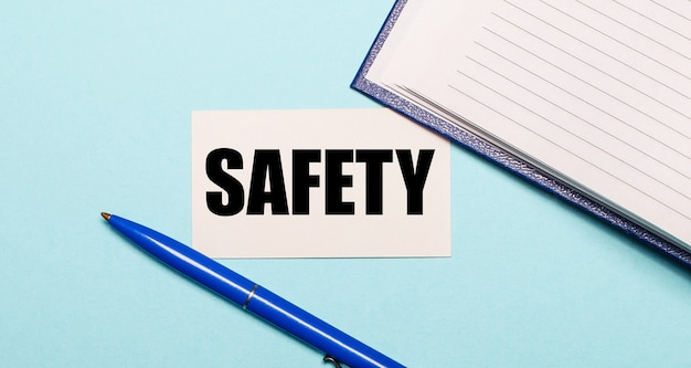 Notizblock, weißer stift und karte mit der aufschrift sicherheit auf blauem hintergrund. sicht von oben