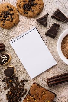 Notizblock zwischen kaffeebohnen, keksen und pralinen