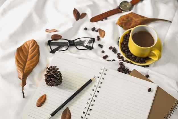 Notizblockbrief-tasse kaffee und ein buch mit einer decke auf einem weißen gewebe im bett.