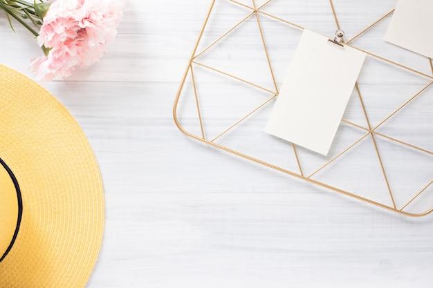 Notizblockcliprahmen und gelber hut des sommers mit blume auf weißer hölzerner tabelle