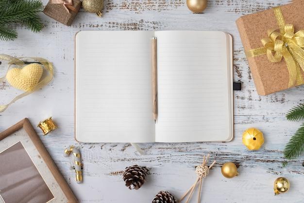 Notizblockpapier des leeren bildschirms mit weihnachtsgeschenkboxen mit goldband und weihnachtsdekorationen auf weißem hölzernem brett.