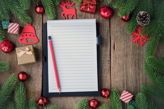 Notizblockpapier des leeren bildschirms mit weihnachtshintergrund mit dekorationen auf hölzernem brett.