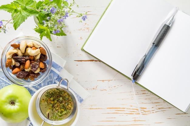 Notizblockstifttelefon und frühstück, weißer hölzerner hintergrund