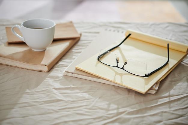 Notizblöcke und planer auf dem bett des studenten sowie gläser und eine tasse kaffee