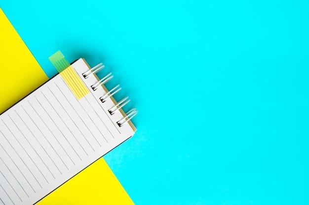 Notizbuch auf blauem und gelbem hintergrund