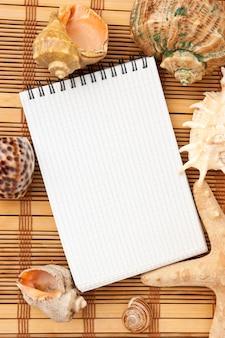 Notizbuch auf dem hintergrund von matten und muscheln