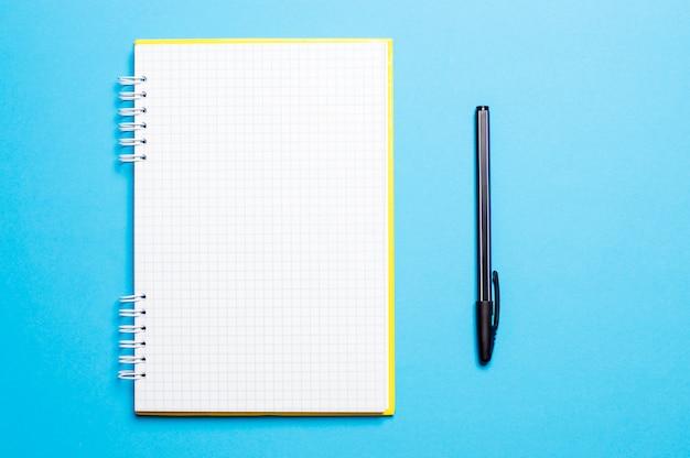 Notizbuch auf einem blauen hintergrund mit stiften