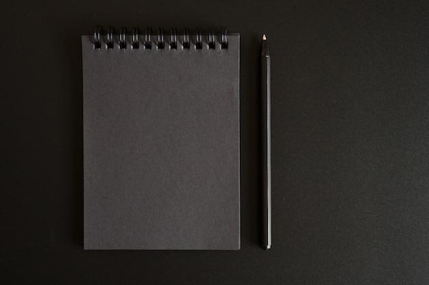 Notizbuch auf einer feder mit schwarzen blättern und einem stift an einer schwarzen wand. platz für text
