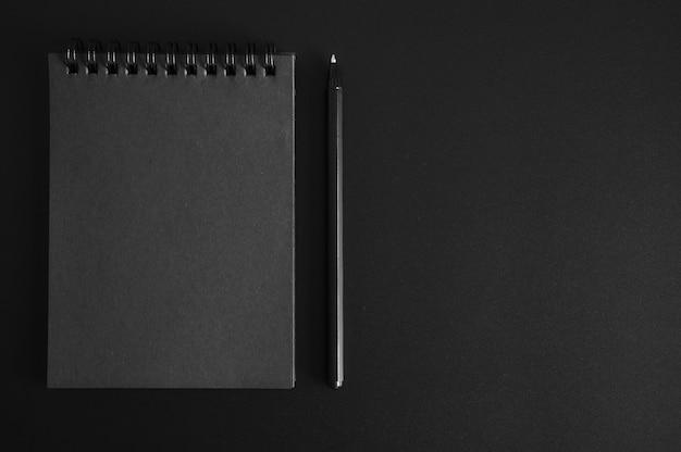 Notizbuch auf einer feder mit schwarzen blättern und einem stift auf schwarz