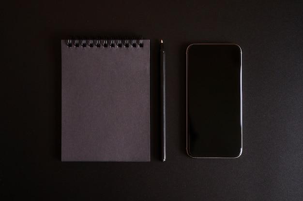 Notizbuch auf einer feder mit schwarzen blättern und einem stift und handy auf einem schwarzen hintergrund.