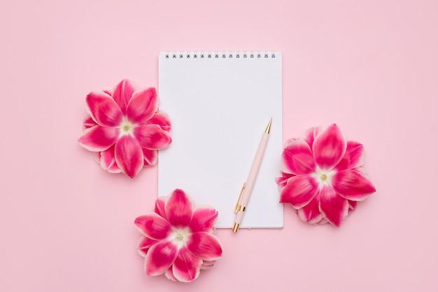 Notizbuch auf einer spirale mit einem leeren weißen blatt, stift und rosa blumen auf einer hellrosa oberfläche