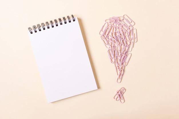 Notizbuch auf einer spirale und rosa büroklammern in form eines ausrufezeichens gegen einen beige hintergrund.