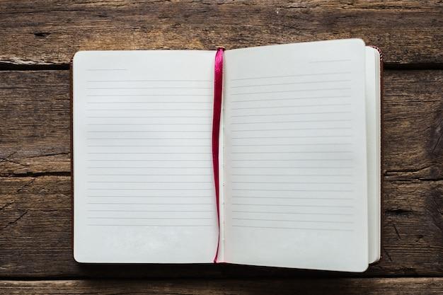 Notizbuch auf hölzernem hintergrund