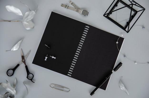Notizbuch auf spirale mit schwarzen blättern auf grauem hintergrund.