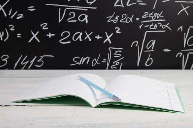 Notizbuch auf tafelhintergrund mit mathematischen formeln