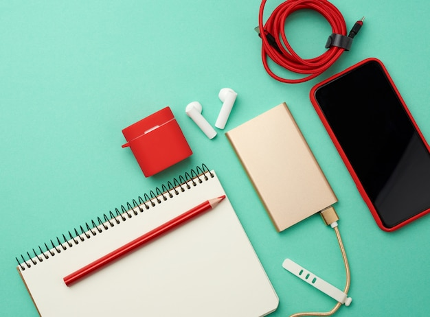 Notizbuch aus papier, power bank mit kabel, rotes smartphone mit leerem schwarzen bildschirm und ohrstöpsel
