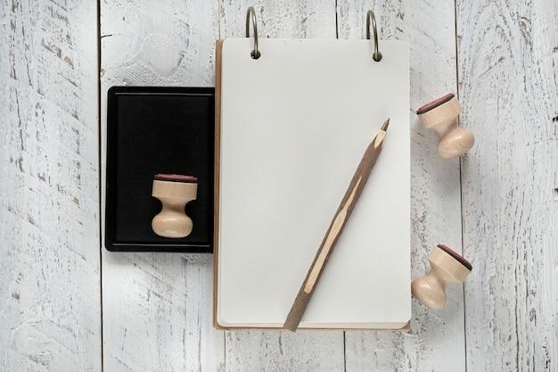 Notizbuch bastelpapier notizblock mit holzstempel und holzstift auf einem weißen schäbigen hintergrund. leerer notizblock leeren