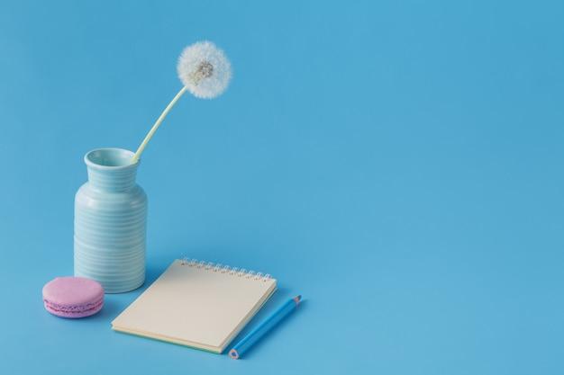 Notizbuch, bleistift, löwenzahn auf blauem schreibtischhintergrund
