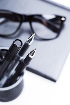 Notizbuch, bleistift und brille