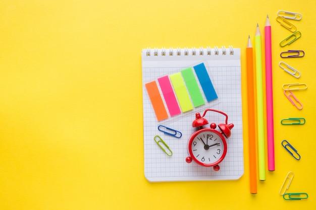 Notizbuch, bleistift und farbige büroklammern, wecker auf gelb
