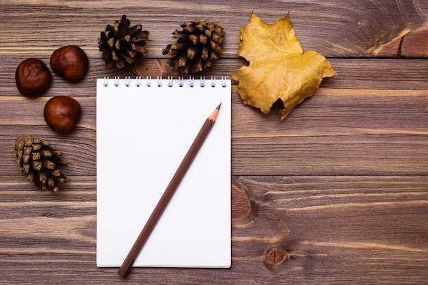 Notizbuch, bleistift und geschenke des herbstes auf einem hölzernen hintergrund.