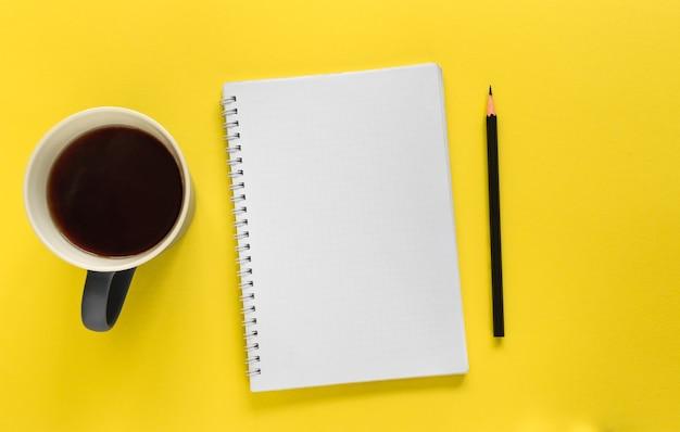 Notizbuch, bleistift und tasse kaffee (tee) auf dem gelben hintergrund. aufgabenliste