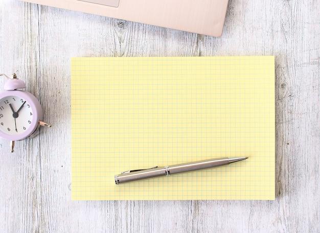 Notizbuch, das auf einem hölzernen arbeitstisch neben einem laptop liegt.