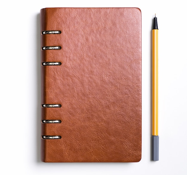 Notizbuch der ledernen abdeckung mit einem gelben stift auf weißem hintergrund