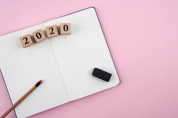 Notizbuch des neuen jahres 2020 auf rosa hintergrund