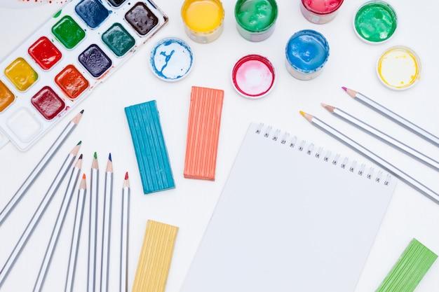 Notizbuch, farben, bleistifte auf weißem hintergrund. zurück zur schule.
