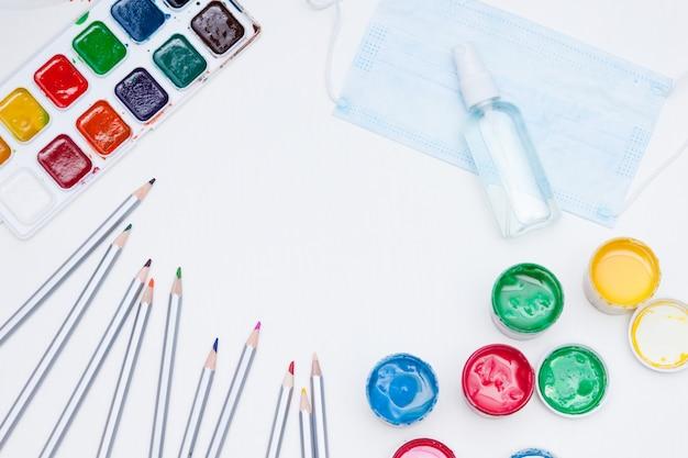 Notizbuch, farben, stifte, desinfektionsgel und medizinische maske