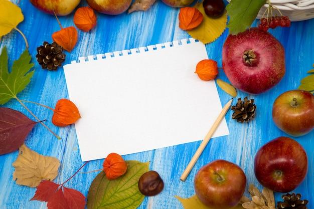 Notizbuch für die inschrift, blumen, blätter und früchte auf einem blauen hölzernen hintergrund