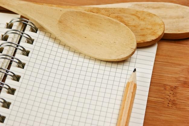 Notizbuch für kulinarische rezepte auf einem küchenschneidebrett