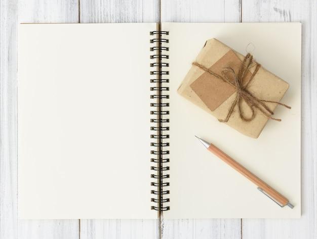 Notizbuch, geschenkbox aus braunem bleistift und pacel auf weißem holztisch, flach gelegt