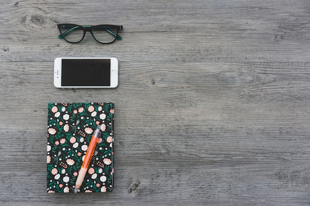 Notizbuch, gläser und handy auf holzoberfläche