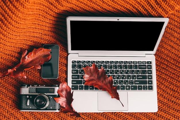 Notizbuch, kamera und telefon auf orange hintergrund. arbeitsplatz
