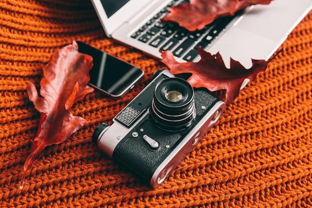 Notizbuch, kamera und telefon auf orange hintergrund. rote blätter auf der tastatur. beruf
