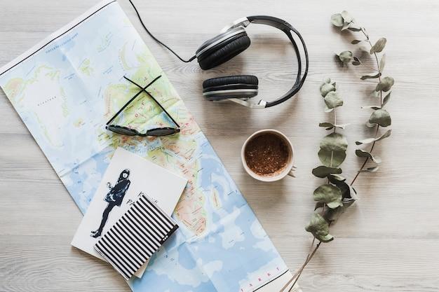 Notizbuch, karte, kaffee und kopfhörer auf dem hölzernen schreibtisch
