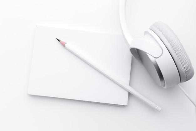 Notizbuch, kopfhörer und bleistift