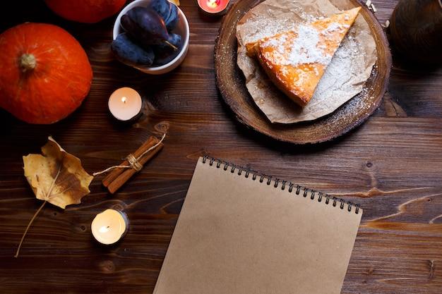 Notizbuch, kürbiskäsekuchen, zu hause gekocht, kürbis, laub, tischlampe, vanille auf einer hölzernen dunklen tabelle