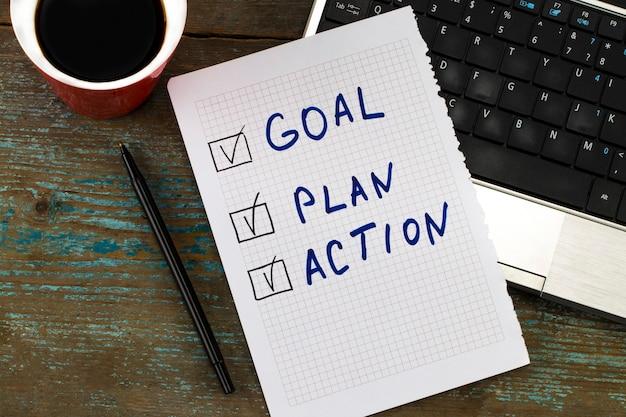 Notizbuch mit aktionsplan. arbeitsplatz mit, kaffee, notizbuch mit aktionsplan und stift auf holztisch.