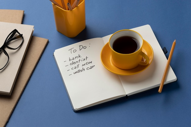 Notizbuch mit aufgabenliste auf dem schreibtisch mit einer tasse kaffee daneben