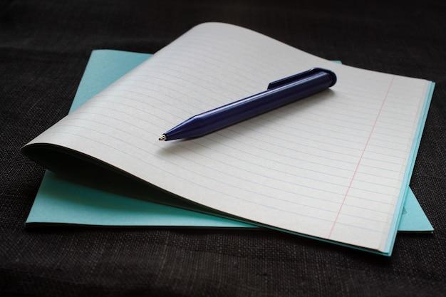 Notizbuch mit begriffspapier und stift auf schwarzem hintergrund