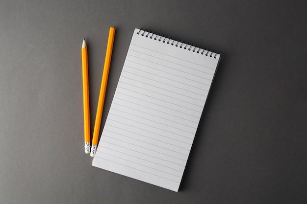 Notizbuch mit bleistift auf grauem hintergrund. bildung, geschäft mit kopienraum. attrappe, lehrmodell, simulation.