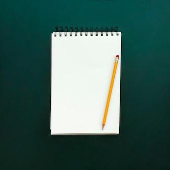 Notizbuch mit bleistift auf grünem schiefer zurück zu schule