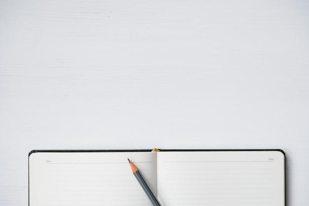 Notizbuch mit bleistift auf weißem holztisch.