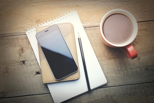 Notizbuch mit bleistift, smartphone und kaffeetasse auf holzuntergrund
