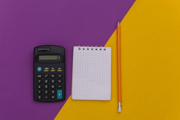 Notizbuch mit bleistift, taschenrechner auf lila gelbem hintergrund. ansicht von oben