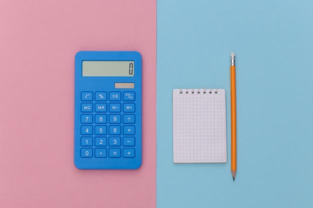 Notizbuch mit bleistift, taschenrechner auf rosa blauem hintergrund. ansicht von oben